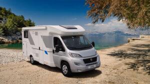 Ein Sun Living S-Serie Wohnwagen steht vor einem idyllischen See an einem sonnigen Tag mit blauen Himmel