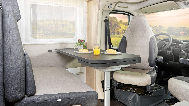 Ein Wohnwagen von innen mit einem Tisch und dem umgedrehten Fahrersitz