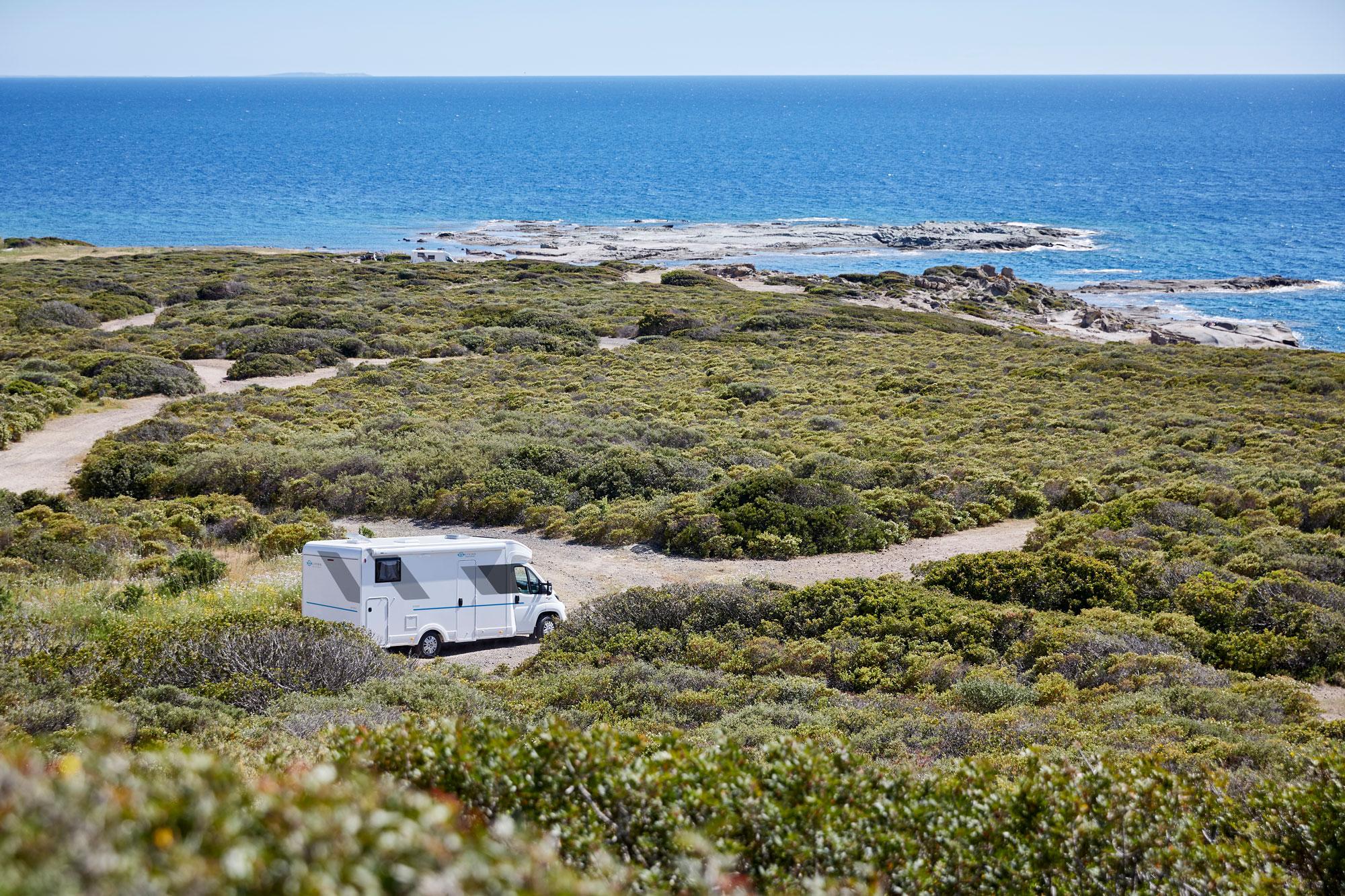 Sun Living Wohnmobil steht vor dem Meer in schroffer Landschaft