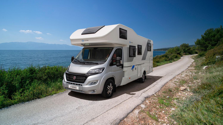 Ein Sun Living A-Serie Wohnwagen steht an einem sonnigen Tag mit blauen Himmel vor dem Meer auf einer Landstrasse